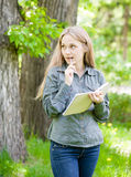 Girl with notebook and pen in park Royalty Free Stock Image