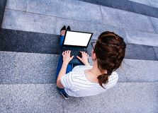 Girl with notebook sitting on the gray steps royalty free stock photography