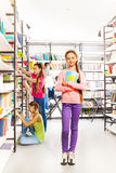 Girl with notebook stands in library near shelves Royalty Free Stock Image