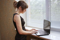 girl with a notebook works on a window-sill Stock Photos