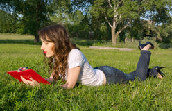 Girl with a notepad and pen in a summer park on the grass Stock Photos