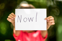 Girl with Now sign Royalty Free Stock Photo