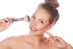 Girl with nude makeup holding makeup brush Stock Photos