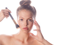 Girl with nude makeup holding makeup brush Royalty Free Stock Images