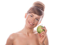 Girl with nude makeup smiling and holding green apple. Royalty Free Stock Photography