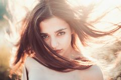 Girl with nude shoulders enjoy her hair waving by wind. Hair care concept.Woman on calm face enjoy sunny and windy day. Nature on background, defocused. Lady stock photo