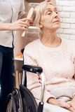 Girl is nursing elderly woman at home. Girl is brushing woman`s hair. stock images