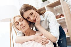 Girl is nursing elderly woman at home. Girl is hugging woman, worried about her. Stock Photography