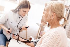 Girl is nursing elderly woman at home. Girl is measuring blood pressure with tonometer. stock photos