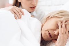 Girl is nursing elderly woman at home. Woman is feeling bad, girl is concerned. stock images
