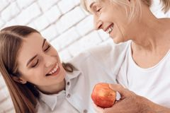 Girl is nursing elderly woman at home. They are embracing. Woman is holding apple. stock image