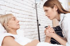 Girl is nursing elderly woman at home. They are holding hands. Girl is concerned. royalty free stock photography