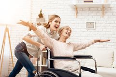 Girl is nursing elderly woman at home. Girl is riding woman in wheelchair. Woman feels like flying. Girl is nursing elderly women at home. Girl is riding women Stock Photo
