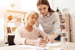Girl is nursing elderly woman at home. Girl is helping woman write. Girl is nursing elderly women in wheelchair at home. Girl is helping women write royalty free stock photo