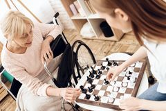 Girl is nursing elderly woman at home. They are playing chess. Girl is nursing elderly women in wheelchair at home. They are playing chess stock photos