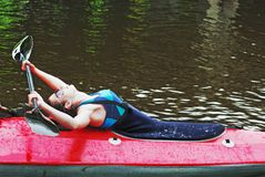 The girl with an oar in a red canoe Stock Photo