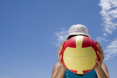 Girl obscuring face with ball outdoors, low angle view Stock Images