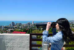 Girl on the observation deck looking into binokol. Stock Image