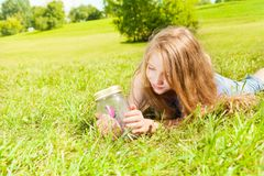 Girl observe. Portrait of happy girl with long dark hair 8 years laying in the grass old hold jar with butterfly looking at the insect Royalty Free Stock Images