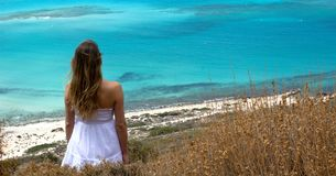 The girl observes the turquoise colored sea Royalty Free Stock Photography