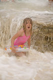 Girl in ocean. A girl with surprised look on her face playing in ocean while wearing her inner tube Stock Images