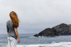 Girl and ocean volcanic island Portugal Azores. Girl looking at atlantic ocean waves volcanic island nature Portugal Azores travel landscape wind hair back royalty free stock photography