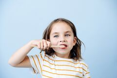 Free Girl Of 5 Years With Bamboo Brush Cleaning Her Teeth On Blue Background Stock Photo - 206559040