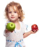 Girl offering an apple. Littel girl with two apples in ahnds, offering the green one Royalty Free Stock Photography