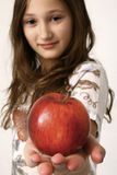 Girl offering apple Royalty Free Stock Photography