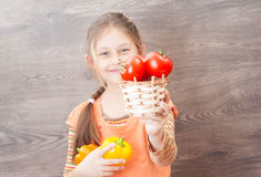 Girl offering a basket of tomatoes Royalty Free Stock Photo