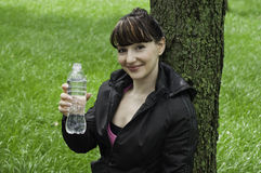 Girl offering a bottle of clear water Stock Images