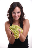Girl offering grapes. A young girl offering green grapes to the camera Royalty Free Stock Photo