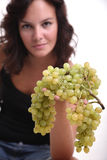 Girl offering grapes. A young girl offering green grapes to the camera Royalty Free Stock Image