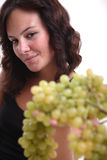 Girl offering grapes. A young girl offering green grapes to the camera Stock Image