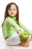 A girl offering a green apple. A barefoot girl in a green shirt offering a green apple Royalty Free Stock Image
