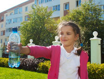 Girl offering a plastic bottle with water Royalty Free Stock Photography