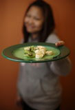 Girl Offering a Plate of Kiwi and Banana. Smiling girl offering a green plate of sliced banana and kiwi Royalty Free Stock Images