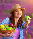 Girl offers an apple. Happy young lady offers an apple, cute gardener girl holding in hands basket with fresh ripe fruits, spending time on backyard, healthy Stock Photography