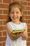 Girl offers book. Girl gives you a book Royalty Free Stock Photos