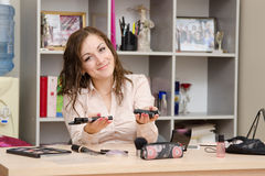 Girl offers cosmetics. Young woman sitting at office table, laid out on the table cosmetics Royalty Free Stock Image