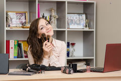 Girl in the office with brushes for make-up. Young woman sitting at office table, laid out on the table cosmetics Stock Image