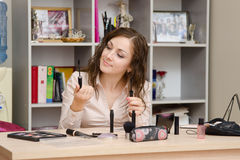 Girl in the office chooses cosmetic mascara. Young woman sitting at office table, laid out on the table cosmetics Stock Image