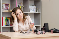 Girl in the office chooses lipstick. Young woman sitting at office table, laid out on the table cosmetics Royalty Free Stock Images