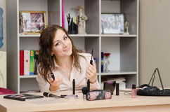 Girl in the office chooses to make up some mascara eyelashes. Young woman sitting at office table, laid out on the table cosmetics Stock Photo