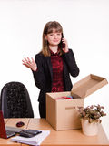 Girl in office collects personal belongings and calling on phone Stock Image