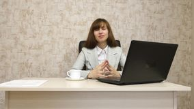 Girl in office at desktop working at the computer and talking. Young female entrepreneur communicates with client. Girl in office at desktop working at computer stock video