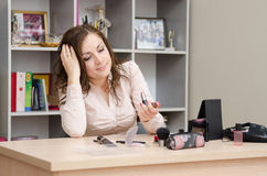 Girl in the office does not know what to use lipstick Royalty Free Stock Photos