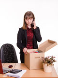 Girl in office examines personal things and calling on phone Royalty Free Stock Images