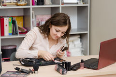 Girl in the office goes through brush beautician Stock Photo