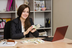 Girl in office happily turns the money a pack Stock Photos